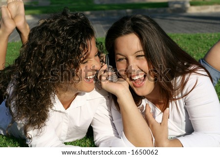 2 girls laughing while listening to cell phone