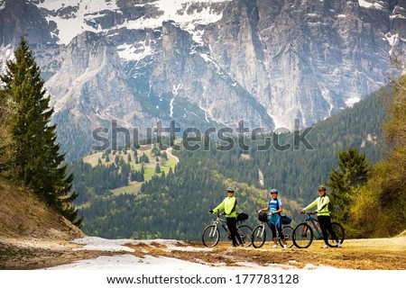 3 Girls with bikes are on the road in the woods and mountains of the Dolomites. Italy. - stock photo