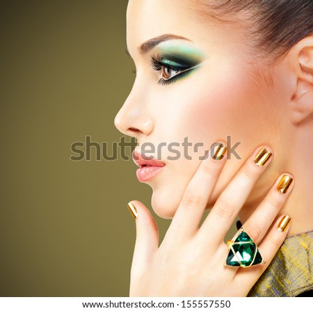 Glamour woman with beautiful golden nails and emerald ring on hands - stock photo
