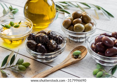 3 glass bowls with different kinds of olives, bottle of olive oil, bowl of olive oil, spoon with olive, framed by olive tree branches on wooden white background. 3 different kinds of olives. Daylight. - stock photo