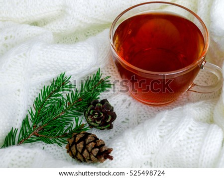 Glass cup of hot tea, dressed in knitted warm scarf winter warm knitted sweater or blanket. Still scarf and a cup of tea with Christmas tree. In the winter time. Cozy and soft winter background.