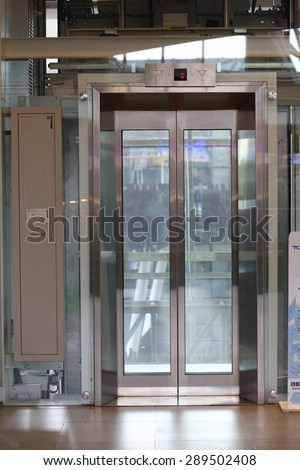 Glass elevator ,Businessman taking modern glass elevator to the upper floors, high building ,office and shopping mall and hotel, transportation