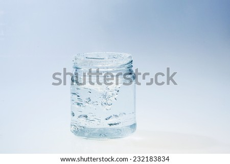 glass jar on blue background with water