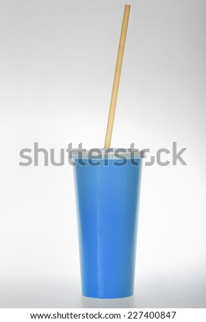 glass of blue paper with a tube on a white background