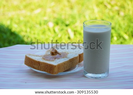 Glass of soy milk add sesame and  bread with peanut butter , blurred background . - stock photo