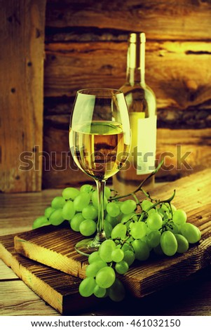 Glass of wine with grape on wooden background.