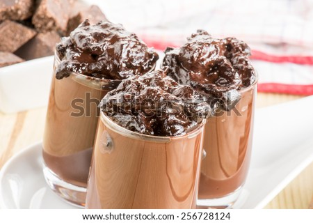 glass with chocolate pudding over a wooden table