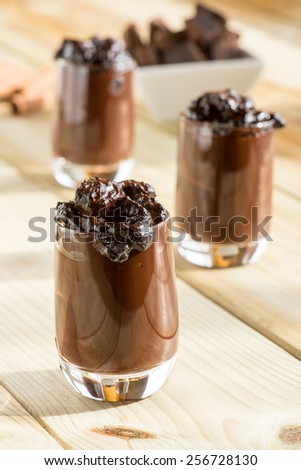 glass with chocolate pudding over a wooden table - stock photo