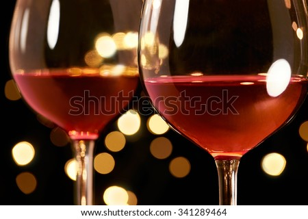 2 glasses of red wine with illumination lights background. Romantic dinner dating night.  - stock photo