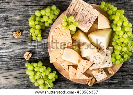 goat cheese with nuts and spices. Green Grapes and walnuts on an old rustic background,  top view