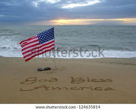 God Bless America handwritten in the sand with an American flag blowing in the breeze - stock photo