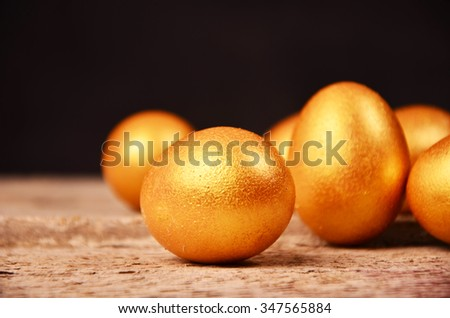 golden eggs on wooden background. investment concept - stock photo