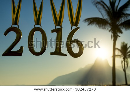 Golden 2016 medals hang from Brazil color ribbons above the Ipanema Beach sunset skyline in Rio de Janeiro, Brazil - stock photo