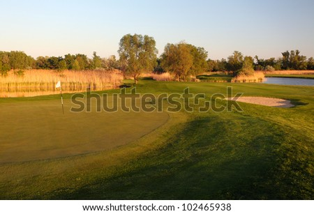 golf course with green grass and trees over blue sky. - stock photo