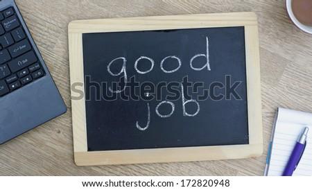 'Good job' written on a chalkboard at the office. - stock photo
