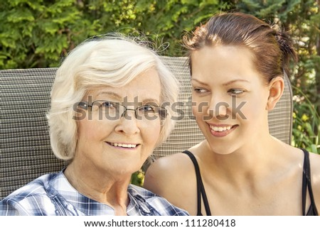 Grandmother and adult granddaughter in the garden - stock photo