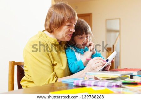 grandmother and  child drawing on paper at home interior. Focus on woman - stock photo