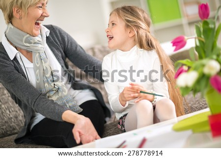Grandmother and cute granddaughter laughing on sofa ta home  - stock photo