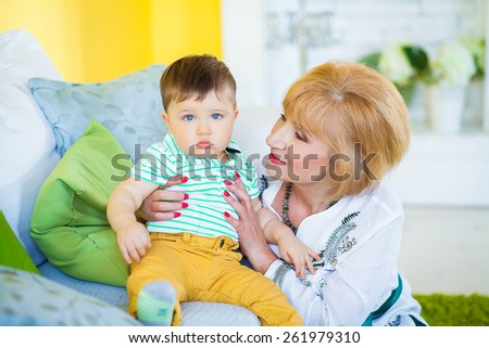 grandmother with a grandson on the couch - stock photo