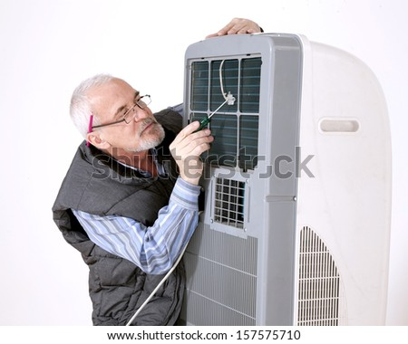 gray-haired man in glasses repairing air conditioning - stock photo