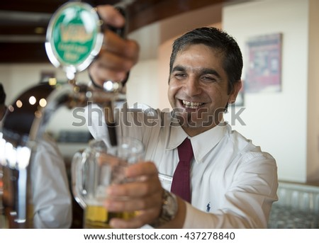 """GREECE. ISLAND RODOS- June 13, 2013. Hotel """"Lindos Imperial Resort."""" . evening restaurant. The bartender pours a beer. Greece, Rhodes  June 13, 2013. - stock photo"""