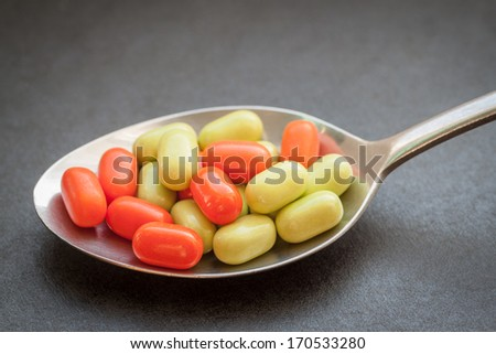 Green and orange candy in metal spoon on dark background. Selective focus with shallow depth of field.   - stock photo