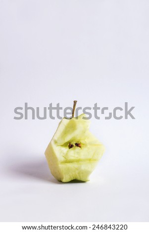 green apple stump isolated on white background; apple stump with eyes and mouth