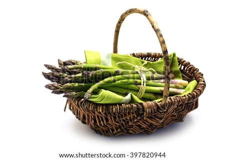green asparagus in a harvest basket, isolated with small shadow on a white background, selected focus - stock photo