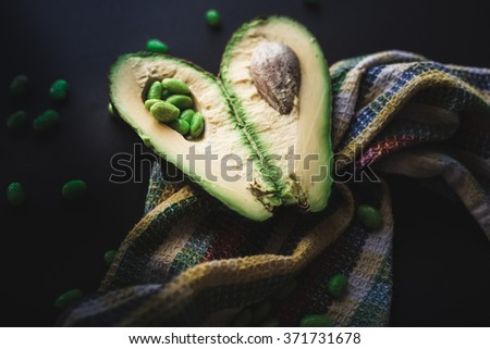 green avocado fruit on a dark background with soy beans called edamame