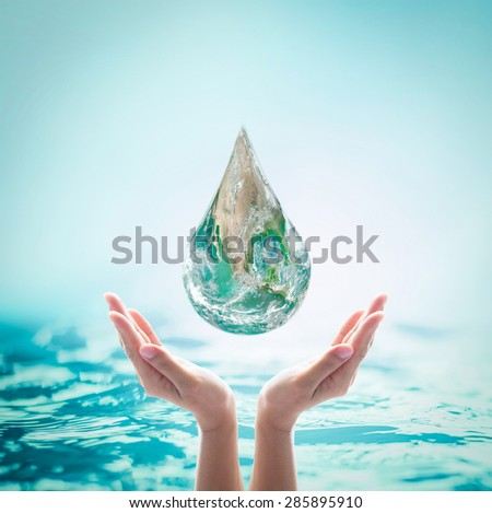 Green planet water droplet above isolated female human hands on turquoise green water background : Saving world environment, ocean and hydrography concept: Elements of this image furnished by NASA - stock photo