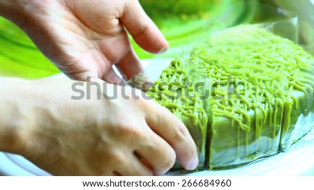 green tea cake , Delicious chocolate cake on plate on table on light background, bakery shop, hand