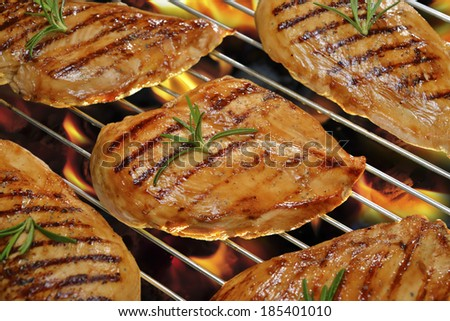 Grilled chicken breast on the flaming grill. - stock photo