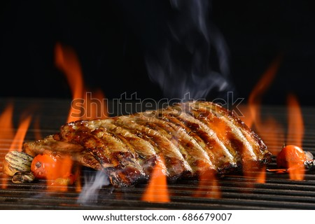 Grilled pork ribs with vegetable on the flaming grill