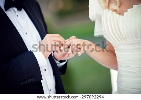 Groom and bride while wedding ceremony, close up on hands exchanging rings  - stock photo