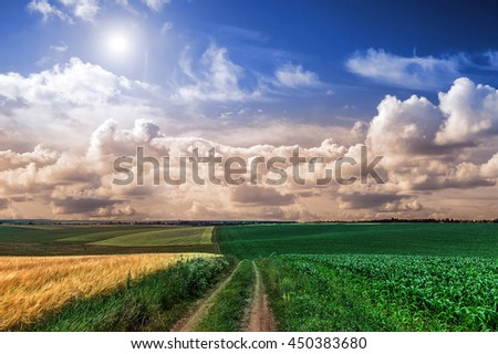 ground road in a rural field. Summer landscape. The idea of the concept of harvest. majestic rural landscape with blue sunny sky and dark storm clouds. creative image. used for creative purposes - stock photo