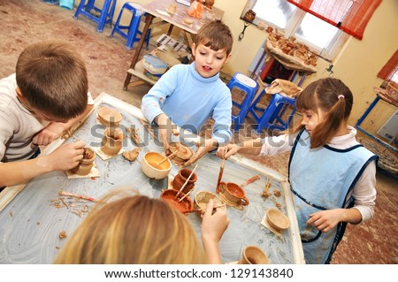 group of children 7-9 years old shaping clay in pottery studio - stock photo