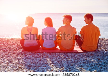 group of friends on the beach at the sunrise. view from the back - stock photo
