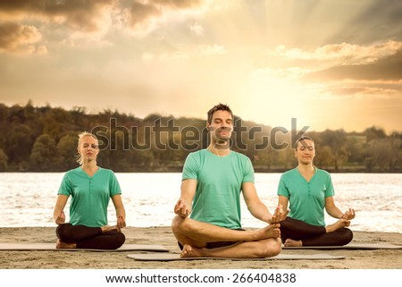 Group of serene people meditating in nature - stock photo