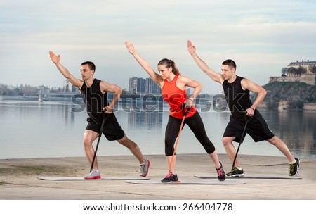 Group of young people doing exercise with resistance rubber