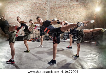 Group of young people  doing kick box exercise, expressing aggression - stock photo
