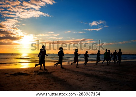 group of young people runs at the beach on beautiful summer - stock photo