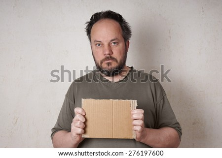 grubby scruffy man holding blank cardboard sign                       - stock photo