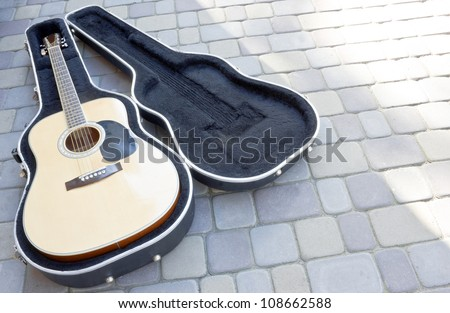 guitar in case resting on the street - stock photo