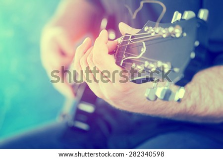 Guitarist on stage in the stagelight - stock photo