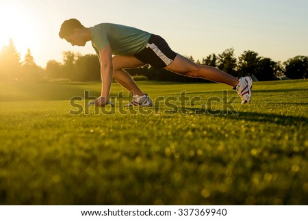 Guy is wrung on the green grass. Athletic man. Guy engaged in sports on the nature. Sport life. - stock photo