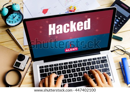 """Hacked"" word on screen laptop display an alert when a man using it on wooden table with camera, clock, calculator and paper graph - hacking, alert and computer concept - stock photo"