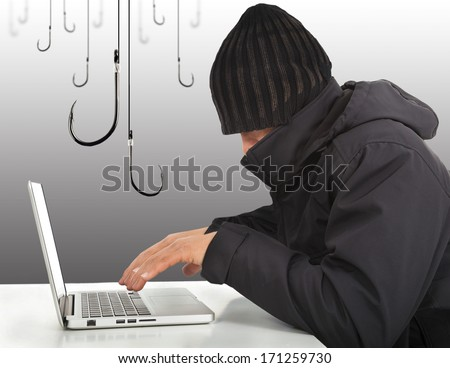 hacker working  with a laptop computer and hooks - stock photo