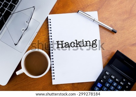 """Hacking"" text on notebook with a cup of coffee, calculator, spectacle and laptop on desk"