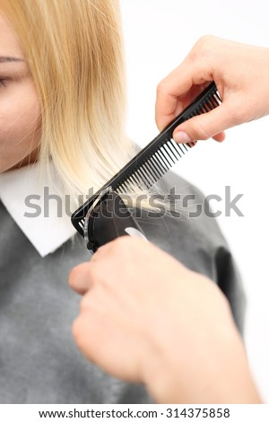 Haircut. Woman hairdresser cuts hair tips