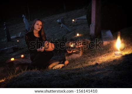 Halloween / Young women in the graveyard - stock photo